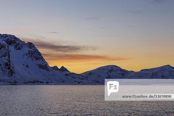 Verschneite Küstenlandschaft bei Sonnenuntergang  Flakstad  Flakstadøy  Lofoten  Nordland  Norwegen  Europa