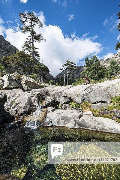Junger Mann sitzt an Gumpe mit kleinem Wasserfall  Gebirge  Fluss Golo  Regionaler Naturpark Korsika  Parc naturel régional de Corse  Korsika  Frankreich  Europa