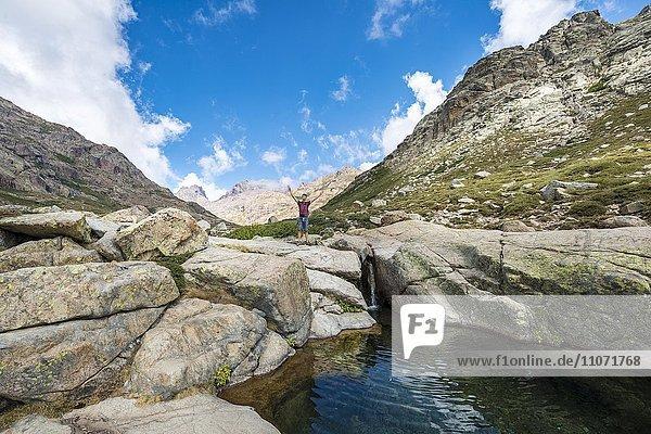 Junger Mann steht an kleinem Wasserfall mit Gumpe  Gebirgslandschaft  Fluss Golo  Regionaler Naturpark Korsika  Parc naturel régional de Corse  Korsika  Frankreich  Europa