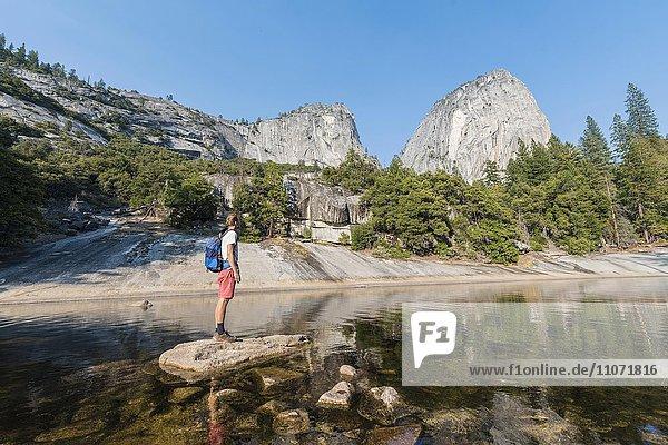Junger Mann steht auf einem Stein mitten im Fluss Merced River  Liberty Cap  Mist Trail  Yosemite-Nationalpark  Kalifornien  USA  Nordamerika