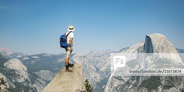 Junger Mann steht auf Felsvorsprung und blickt auf den Half Dome  Ausblick vom Glacier Point  Yosemite Nationalpark  Kalifornien  USA  Nordamerika