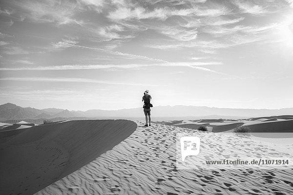 Junger Mann  Tourist fotografiert Sanddünen  Mesquite Flat Sand Dunes  hinten Amargosa-Range Bergkette  Death Valley  Death-Valley-Nationalpark  Kalifornien  USA  Nordamerika