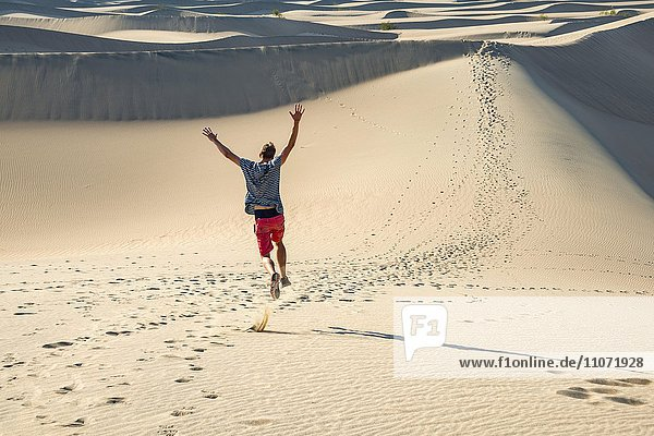 Junger Mann  Tourist läuft eine Sanddüne hinunter  Mesquite Flat Sand Dunes  Sanddünen  Death Valley  Death-Valley-Nationalpark  Kalifornien  USA  Nordamerika
