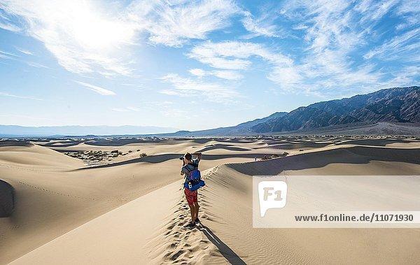Junger Mann  Tourist fotografiert Sanddünen  Mesquite Flat Sand Dunes  hinten Ausläufer der Amargosa-Range Bergkette  Death Valley  Death-Valley-Nationalpark  Kalifornien  USA  Nordamerika