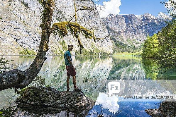 Junger Mann steht auf einem Stein im Wasser  Obersee mit Wasserspiegelung  Salet am Königssee  Nationalpark Berchtesgaden  Berchtesgadener Land  Oberbayern  Bayern  Deutschland  Europa