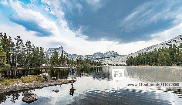 Wanderin steht an einem See  Lower Cathedral Lake  Sierra Nevada  Yosemite Nationalpark  Kalifornien