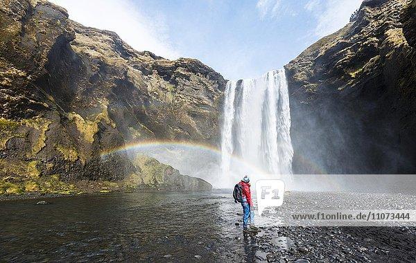 Wanderer vor Wasserfall Skogafoss mit Regenbogen  Skogar  Süd Island  Island  Europa