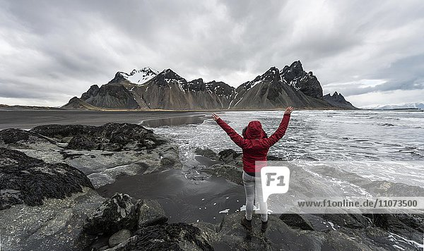 Hiker with arms outstretched  mountains Klifatindur  Eystrahorn and Kambhorn  Stokksnes headland  Klifatindur mountain range  Eastern Region  Iceland  Europe