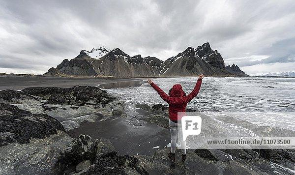 Wanderin streckt Arme nach oben  Berge Klifatindur  Eystrahorn und Kambhorn  Landzunge Stokksnes  Bergmassiv Klifatindur  Austurland  Ostisland  Island  Europa