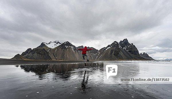 Wanderin springt am Strand  Berge Klifatindur  Eystrahorn und Kambhorn  Landzunge Stokksnes  Bergmassiv Klifatindur  Austurland  Ostisland  Island  Europa