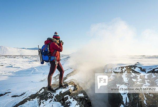 Frau steht an Kontinentalspalte zwischen Nordamerikanischer und Eurasischer Platten  und fotografiert  Mittelatlantischer Rücken  Grabenbruch  Krafla  Mývatn  Nordisland  Island  Europa