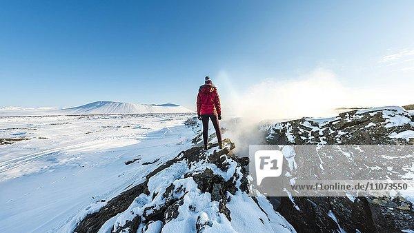 Frau steht an Kontinentalspalte zwischen Nordamerikanischer und Eurasischer Platten  Mittelatlantischer Rücken  Grabenbruch  Krafla  Mývatn  Nordisland  Island  Europa