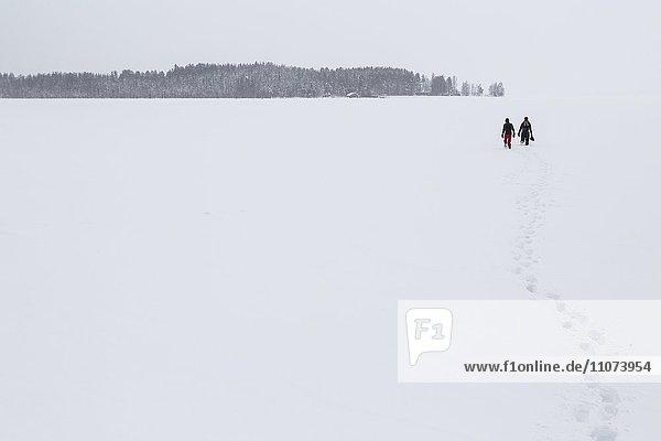Zwei Menschen laufen über zugefrorenen See am Polarkreis  vorne Fußspuren  Kivilompolio  Nähe Rovaniemi  Lappland  Finnland  Europa