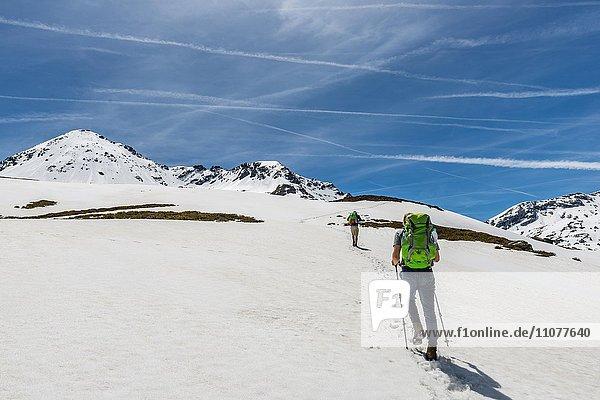 Zwei Wanderer wandern über Schneefeld  Rohrmoos-Untertal  Schladminger Tauern  Schladming  Steiermark  Österreich  Europa