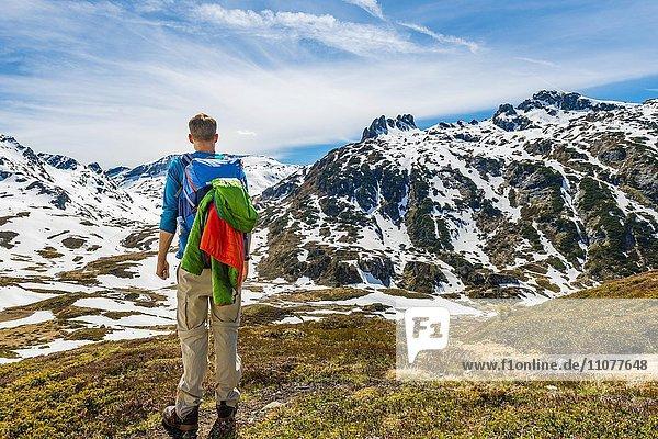 Junger Mann  Wanderer schaut in die Ferne  Berglandschaft mit Schneeresten  Rohrmoos-Untertal  Schladminger Tauern  Schladming  Steiermark  Österreich  Europa