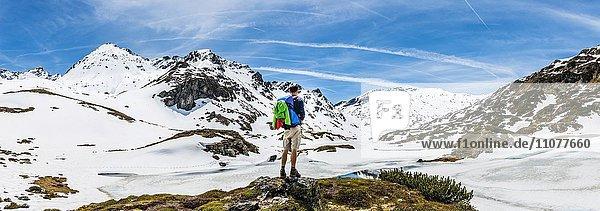 Wanderer steht vor Berglandschaft  Schneereste  Rohrmoos-Untertal  Schladminger Tauern  Schladming  Steiermark  Österreich  Europa