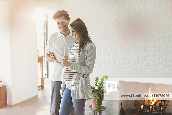 Schwangeres Paar mit digitalem Tablett in der Nähe des Kamins