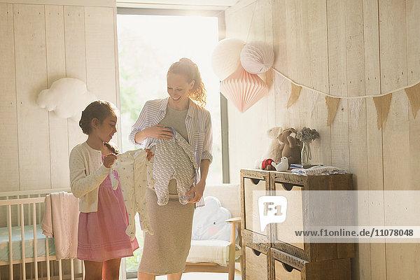 Schwangere Mutter und Tochter mit Babykleidung im Kinderzimmer Schwangere Mutter und Tochter mit Babykleidung im Kinderzimmer