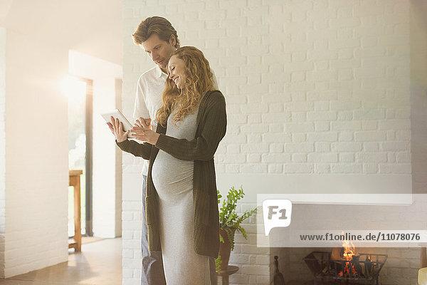 Schwangere Paare  die ein digitales Tablett in der Nähe eines Kamins im Wohnzimmer benutzen.