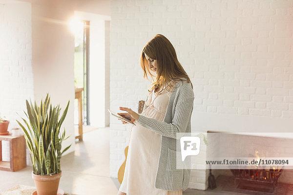 Schwangere Frau mit digitalem Tablett am Kamin im Wohnzimmer Schwangere Frau mit digitalem Tablett am Kamin im Wohnzimmer