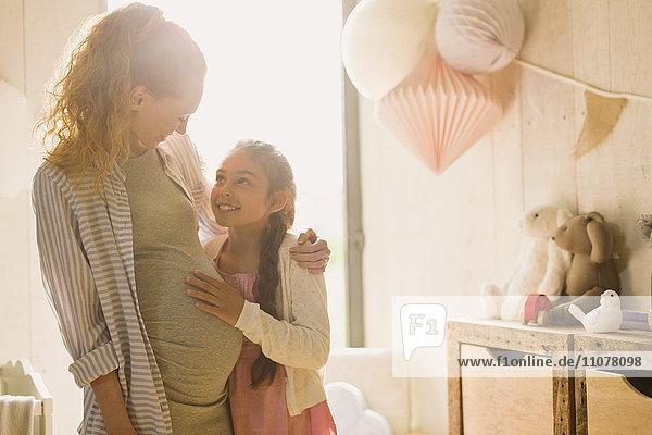 Schwangere Mutter und Tochter im sonnigen Kinderzimmer