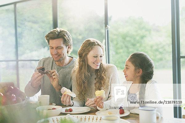 Familie isst Muffins am Tisch