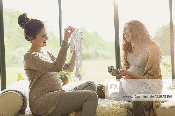 Eine schwangere Frau zeigt ihrem Freund Babykleidung. Eine schwangere Frau zeigt ihrem Freund Babykleidung.