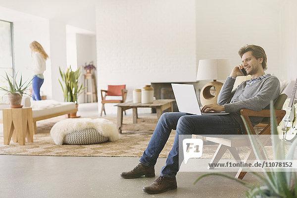 Mann spricht am Handy und benutzt Laptop im Wohnzimmer