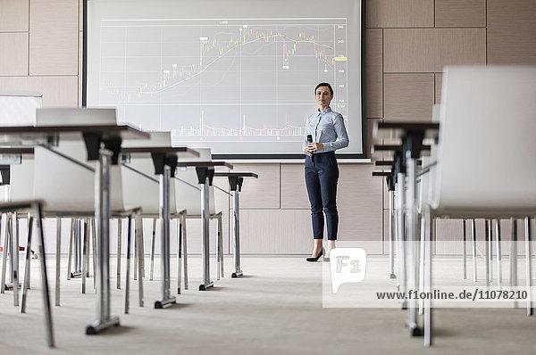 Porträtbewusste Geschäftsfrau mit Mikrofon an der Projektionswand mit Diagramm im Konferenzraum
