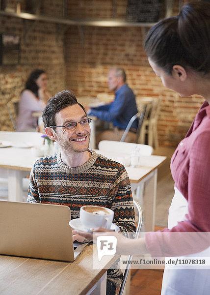Barista serviert Cappuccino an lächelnden Mann am Laptop im Cafe
