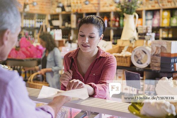 Frau probiert Käse an der Feinkosttheke im Markt