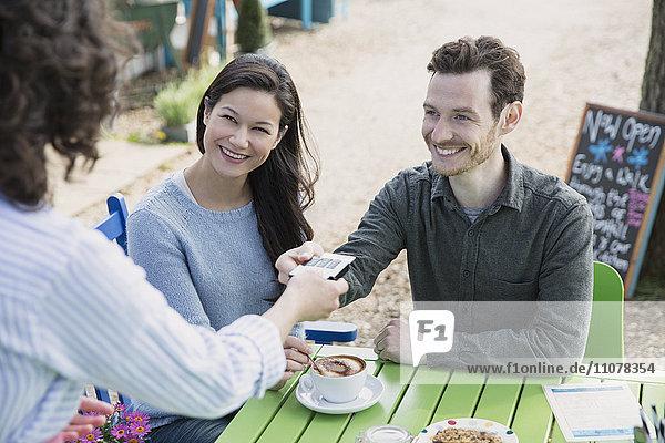 Kellnerin übergibt Kreditkartenleser zum Koppeln im Außencafé