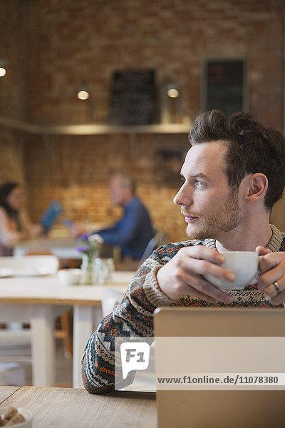 Nachdenklicher Mann beim Kaffeetrinken am Laptop im Cafe