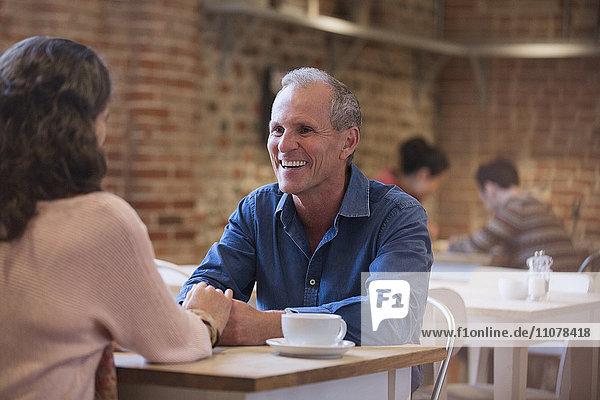 Lächelndes Paar hält Händchen und redet im Cafe