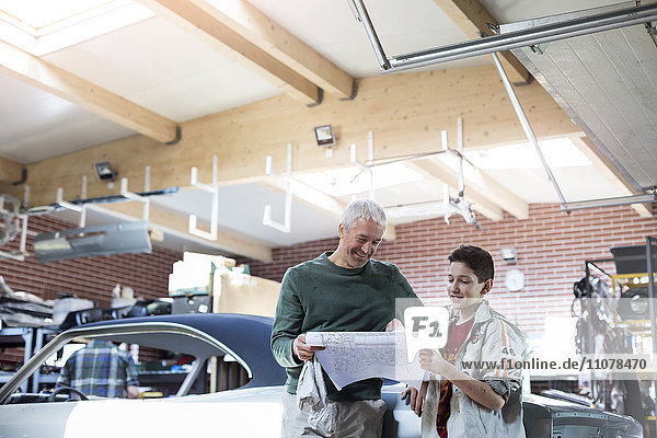 Father and son reviewing plans in auto repair shop