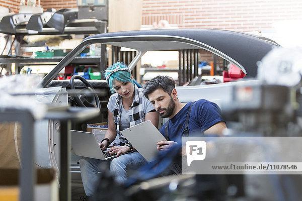 Mechaniker arbeiten mit Zwischenablage und Laptop in der Autowerkstatt