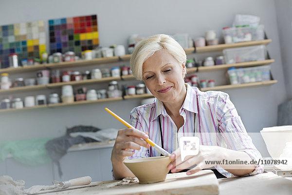 Lächelnde reife Frau malt Töpferschale im Atelier