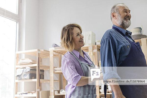 Lächelnde Ehefrau beim Binden der Schürze im Töpferatelier