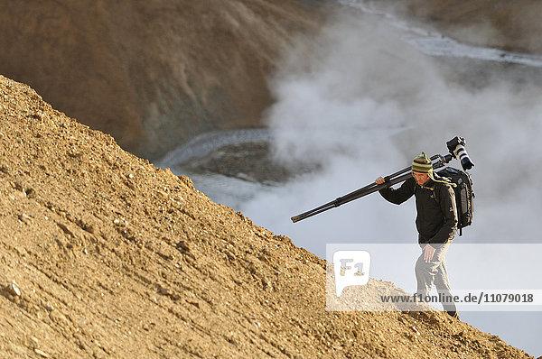 Photographer walking uphill