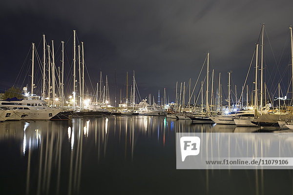 View of harbour at night with moored boats