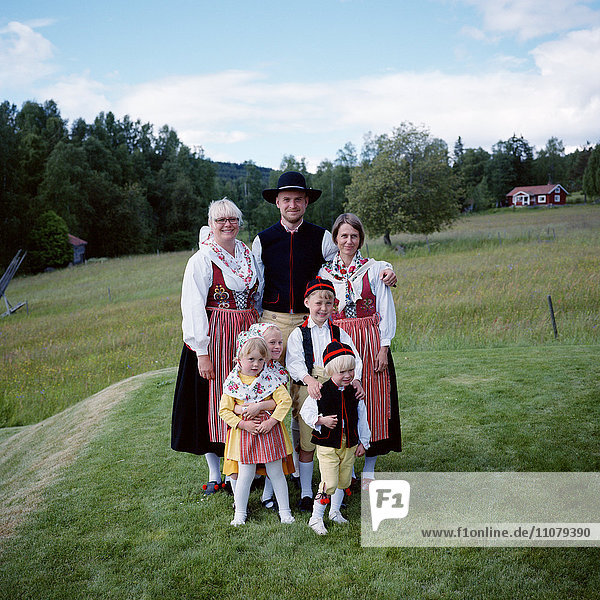 Family in traditional clothing standing on grass field  smiling