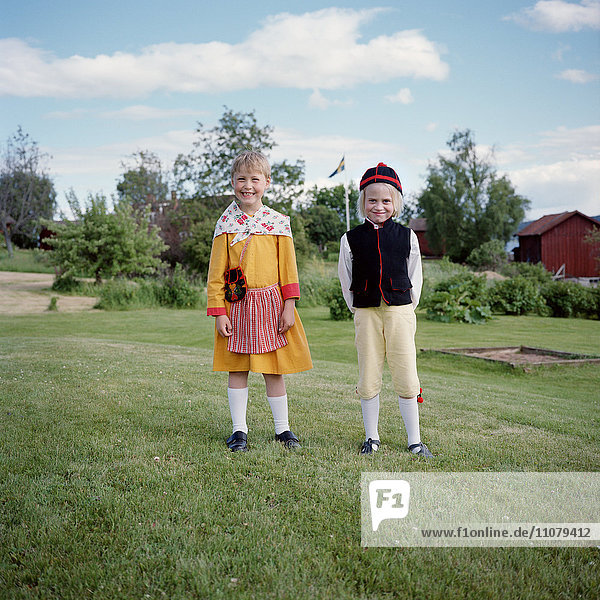 Boy and girl in traditional clothing  smiling  portrait