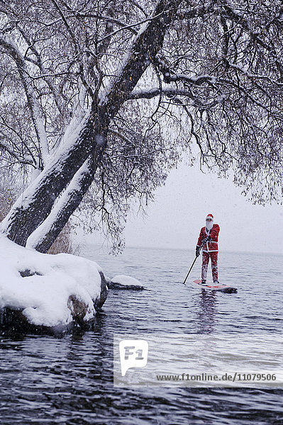 Man dressed as Santa Claus paddling on lake