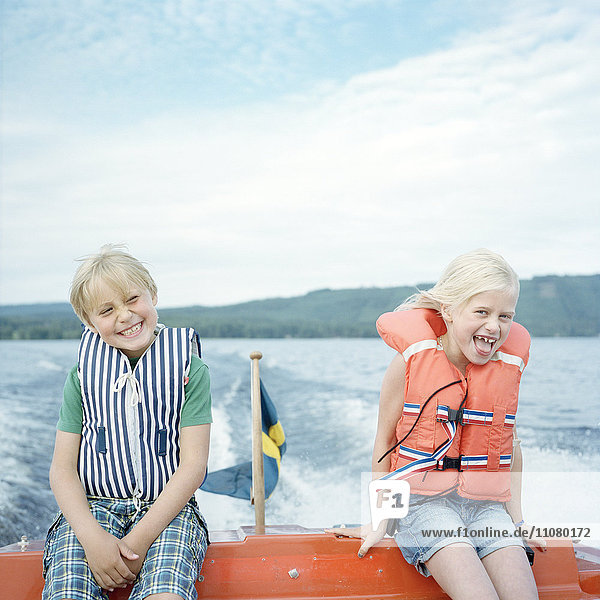 Portrait of two laughing sisters on boat