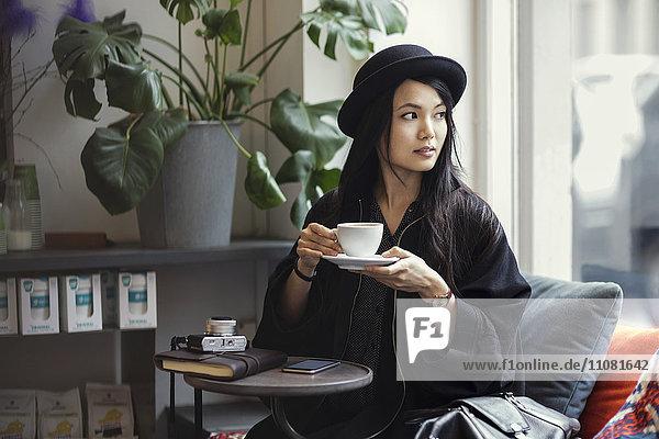 Nachdenkliche junge Frau mit Kaffeetasse im kreativen Büro am Fenster sitzend