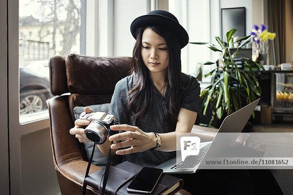 Unternehmerin mit Kamera im Sitzen mit Laptop auf dem Stuhl