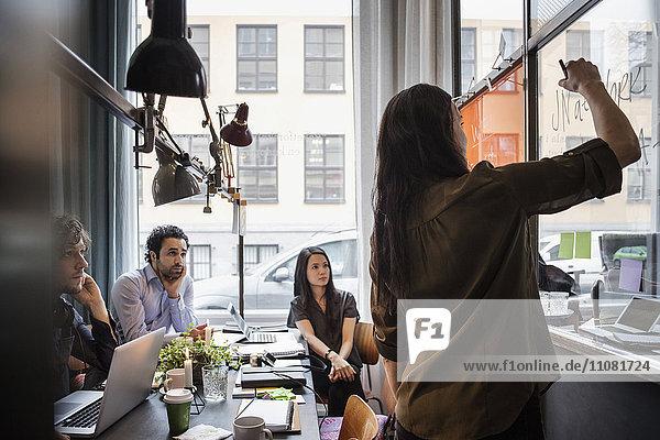Kreative Geschäftsleute  die weibliche Mitarbeiterin beim Schreiben auf Glas im Büro anschauen