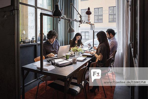 Bloggerinnen und Blogger arbeiten am Tisch im modernen Büro
