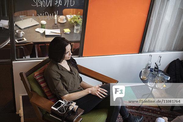 Großer Blickwinkel auf die kreative Geschäftsfrau auf dem Stuhl im Büro