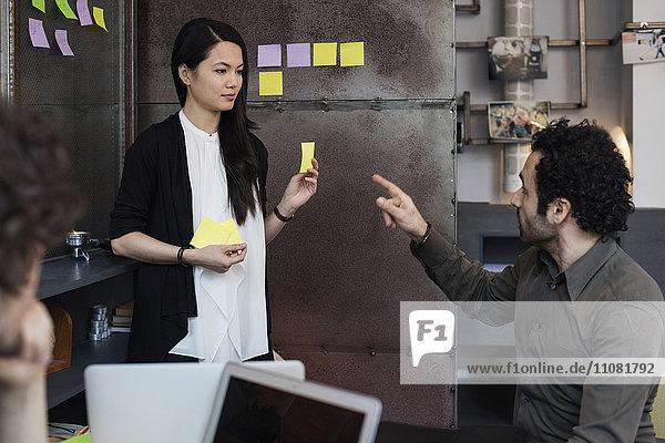 Kreativer Geschäftsmann im Gespräch mit Mitarbeiterin im Büro